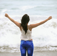 More Balanced Living - woman, arms outstretched in front of sea