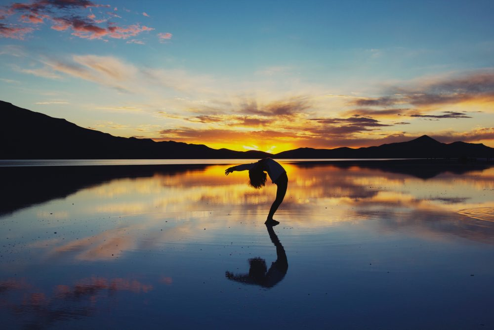 Yoga Hen Party - girl doing yoga pose on lake shore at sunrise